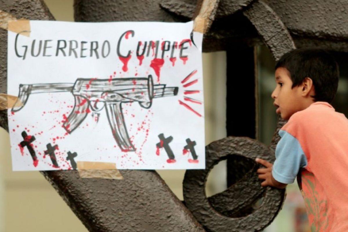 Un niño mira un cartel con el mensaje 'Guerrero cumple', durante una protesta de profesores por la muerte de seis personas en Chilpancingo, en el estado mexicano de Guerrero, el 27 de septiembre de 2014 Foto:Pedro Pardo/afp.com