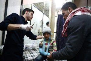 Un hombre sirio sostiene la mano de un niño que espera que le curen las heridas provocadas por un ataque áreo contra un barrio rebelde, en un hospital de campaña de Duma, cerca de Damasco, el 25 de noviembre de 2016 Foto:Abd Doumany/afp.com