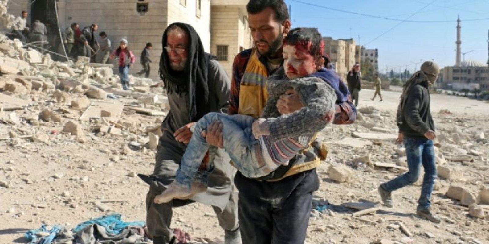 Un voluntario de defensa civil carga con un niño rescatado entre los escombros de un edificio tras un presunto ataque con bombas de barril al barrio de Bab al Nairab, el pasado 24 de noviembre en la ciudad siria de Alepo Foto:Ameer Alhalbi/afp.com