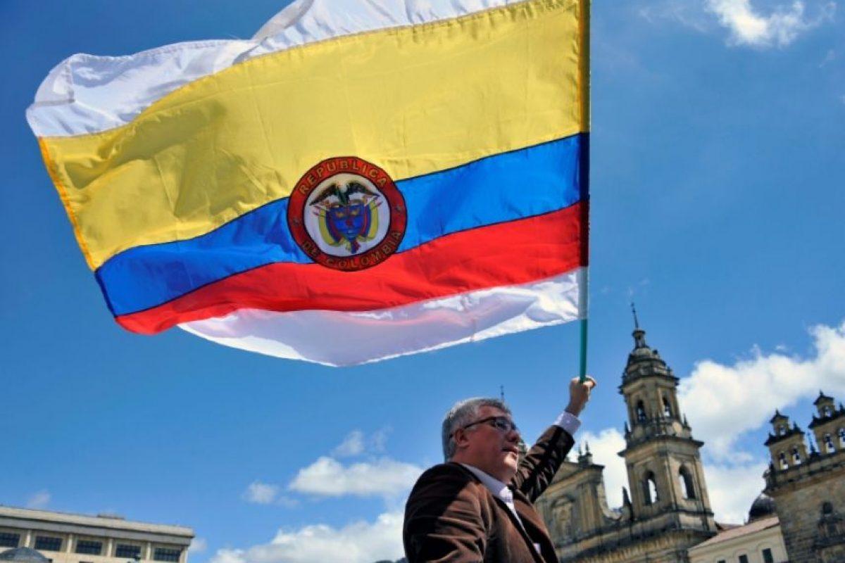Un hombre lleva una bandera nacional colombiana con franjas blancas durante una manifestación para exigir el respaldo al nuevo acuerdo de paz entre el gobierno colombiano y las FARC fuera del Congreso colombiano, el 30 de noviembre de 2016 en Bogotá Foto:GUILLERMO LEGARIA/afp.com