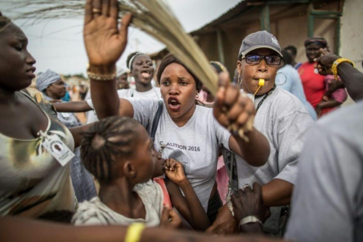 Una seguidora de Adama Barrow, candidata presidencial de la coalición opositora en Gambia, calma a sus compañeros tras un encontronazo con varios simpatizantes del actual presidente, Yahya Jammeh, en una marcha en Banjul, el 27 de noviembre de 2016 Foto:Marco Longari/afp.com