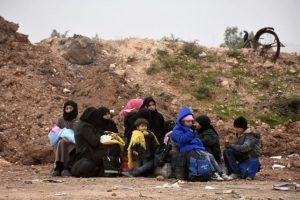 Unos sirios huidos del este de Alepo se sientan al borde de una carretera tras llegar al punto de cruce de Jabal Badro, recientemente recuperado por las fuerzas del régimen, el 30 de noviembre de 2016 Foto:George Ourfalian/afp.com