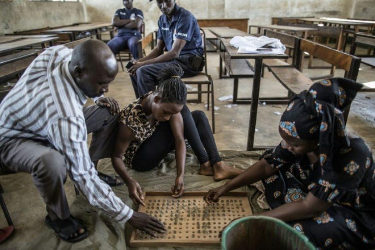 Unos encargados de una mesa electoral en el barrio de Tallinding, en Serekunda (Gambia), cuentan las canicas con las que votarán los electores en los comicios presidenciales, el 30 de noviembre de 2016, víspera de la votación Foto:Marco Longari/afp.com