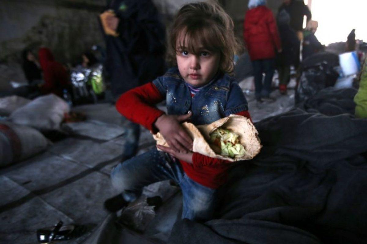 Una niña siria huida de las zonas rebeldes de Alepo junto a su familia sostiene comida entre los brazos el 30 de noviembre de 2016 en un refugio del barrio de Jibrin Foto:Youssef Karwashan/afp.com