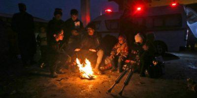 Sirios desplazados por el avance de tropas rebeldes en Alepo se sientan alrededor de un fuego para calentarse en su refugio de Jibrin, al este de la ciudad siria, el 30 de noviembre de 2016 Foto:Youssef Karwashan/afp.com