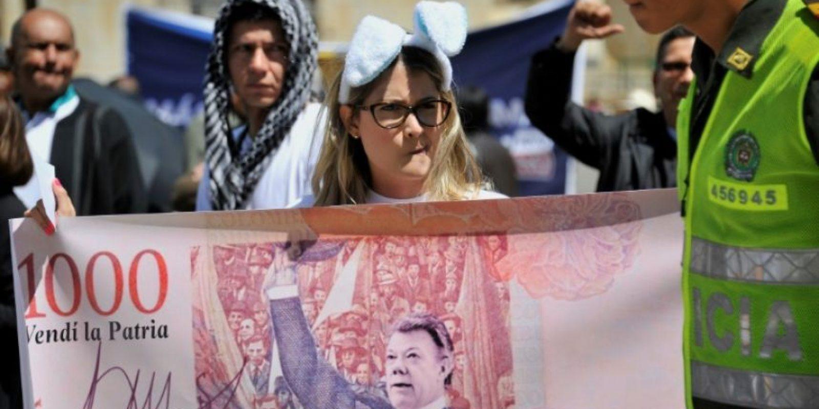 Una mujer sujeta una pancarta con la efigie del presidente de Colombia, Juan Manuel Santos, durante una protesta en contra del nuevo acuerdo de paz del Gobierno con las FARC, en Bogotá, el 30 de noviembre de 2016 Foto:Guillermo Legaria/afp.com