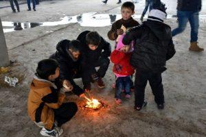 Un grupo de niños huidos de las zonas rebeldes del este de Alepo encienden un fuego en un almacén convertido en albergue, este jueves 1 de diciembre en Duweirineh, un pequeño pueblo a las afueras de la ciudad siria Foto:George Ourfalian/afp.com