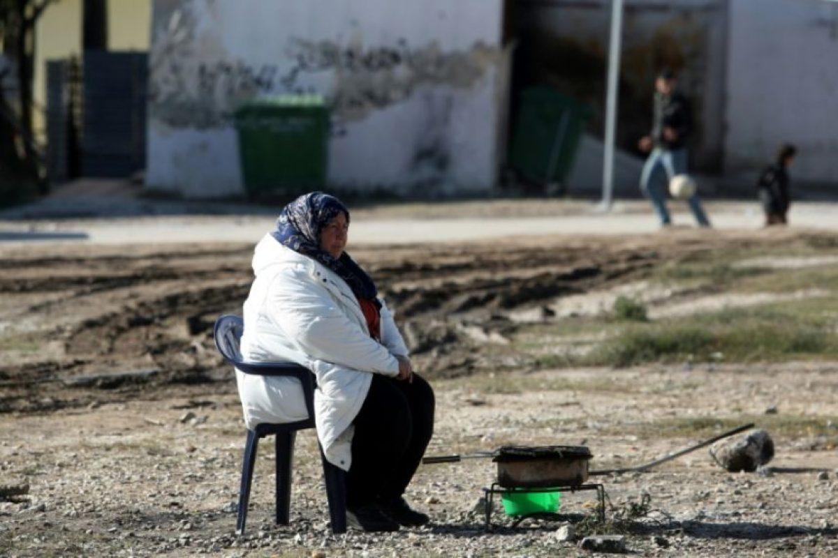 Una mujer calienta su comida en un campo de refugiados en Salónica (Grecia), el 1 de diciembre de 2016 Foto:Sakis Mitrolidis/afp.com
