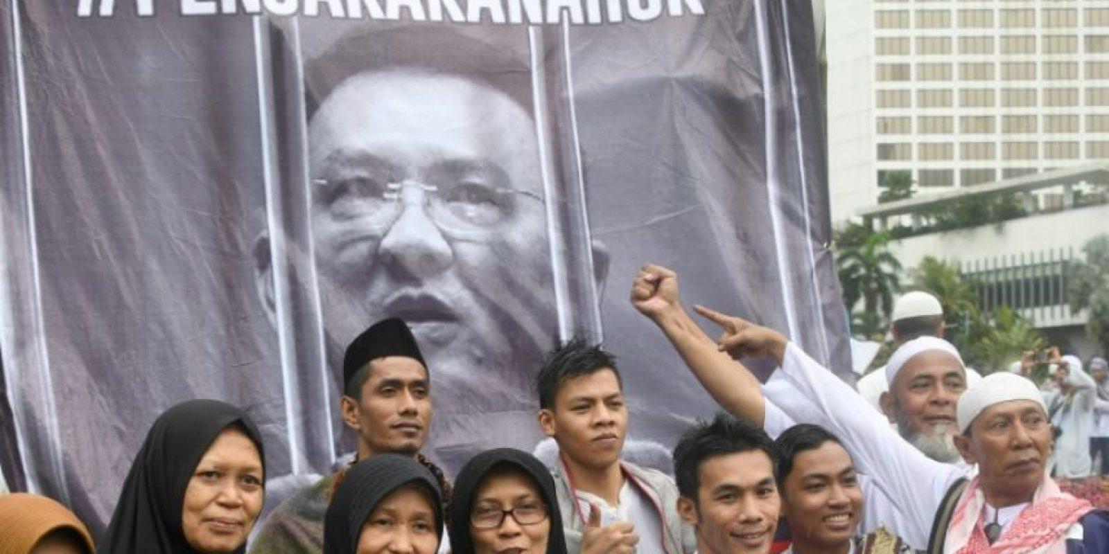 Unos indonesios posan frente a un póster de Basuki Tjahaja Purnama, conocido como Ahok, tras una manifestación en contra de este gobernador, en Yakarta, el 2 de diciembre de 2016 Foto:Goh Chai Hin/afp.com