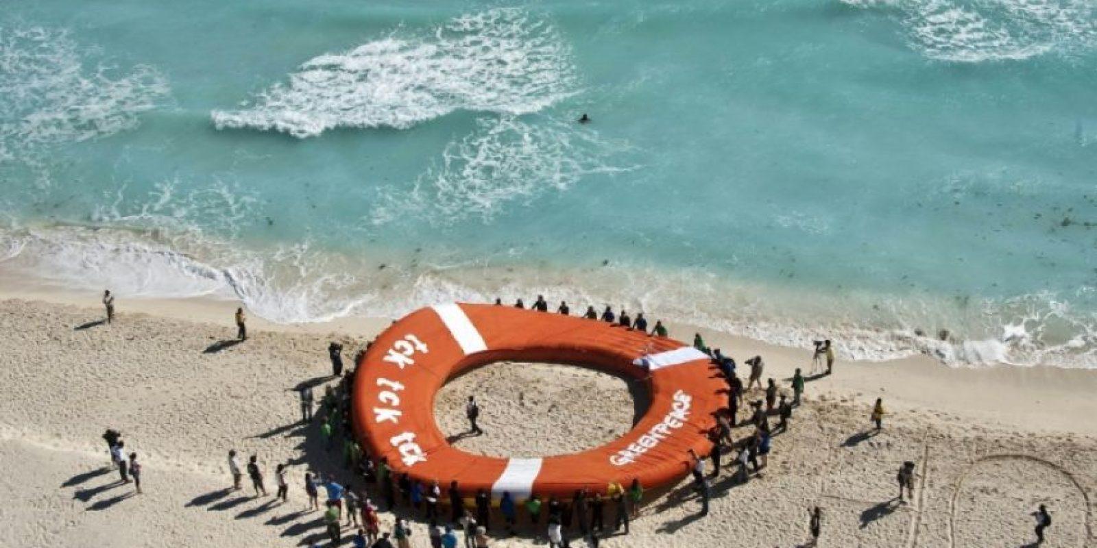Miembros de la ONG ecologista Greenpeace se manifiestan usando un salvavidas gigante, en una playa de Cancún, México, en el marco de la conferencia COP13 del Convenio sobre la Diversidad Biológica en Cancún, México, el 2 de diciembre de 2016. Foto:Ronaldo Schemidt/afp.com