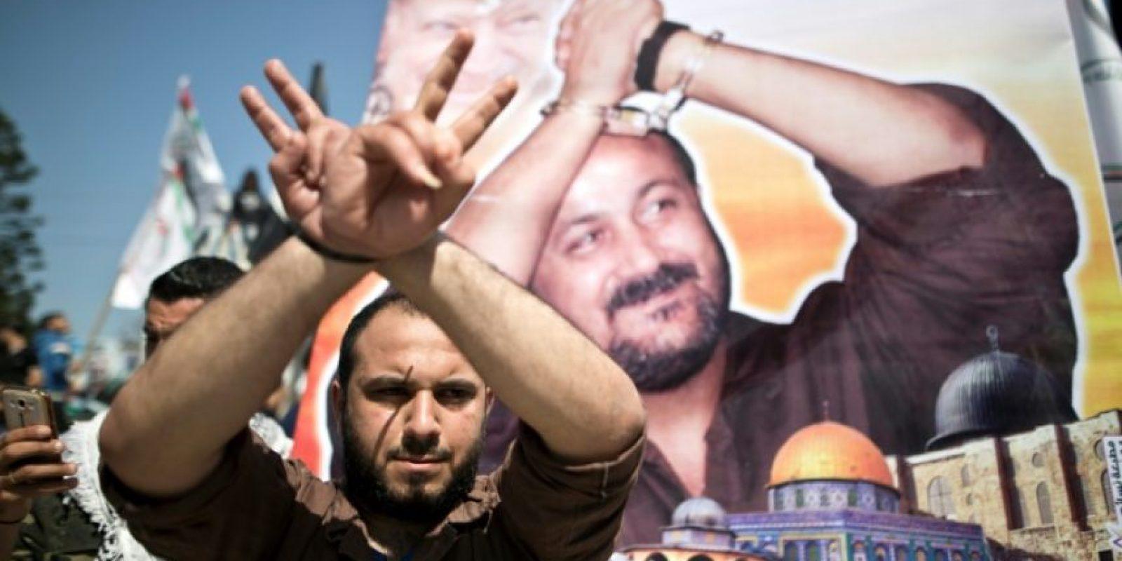 Un hombre palestino hace señas con sus manos frente a un cartel que lleva el retrato del líder de Fatah encarcelado Marwan Barghuti, durante una manifestación que marca el Día del Prisionero Palestino en la Ciudad de Gaza, el 17 de abril de 2016. Foto:MAHMUD HAMS/afp.com