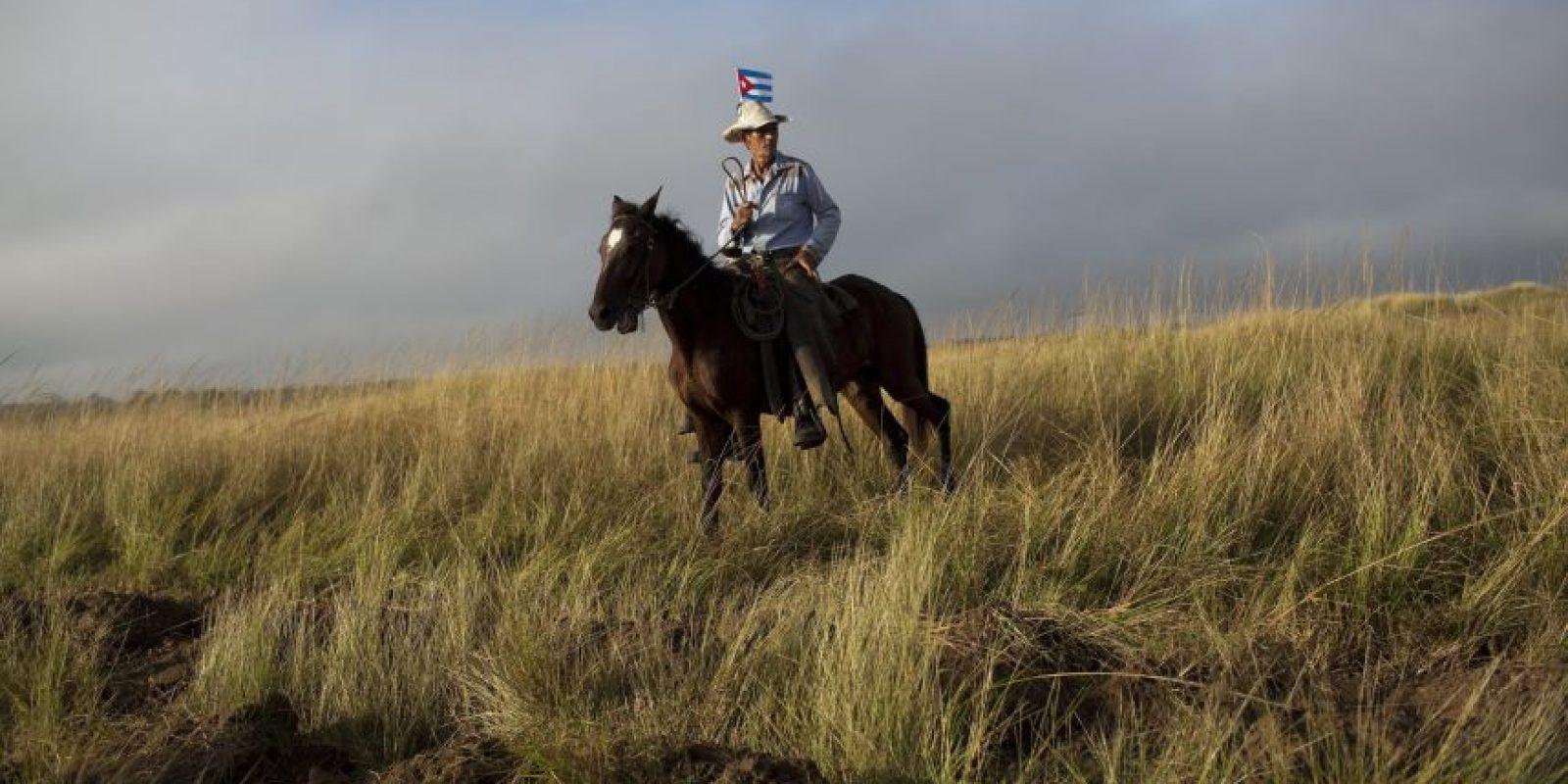 En esta foto del 2 de diciembre de 2016, un hombre aguarda sobre su caballo el paso de la caravana con las cenizas del líder Fidel Castro en Las Tunas, Cuba. En los caminos solitarios del oriente de Cuba, la gente esperó por horas para saludar la urna con los restos del expresidente cubano. Foto:Rodrigo Abd / AP Foto