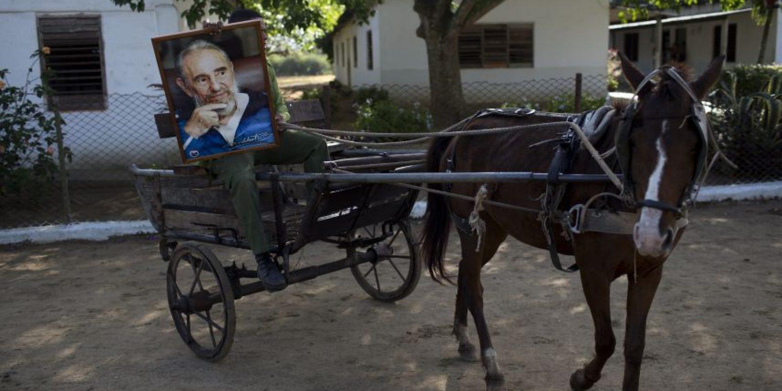 En esta foto del 30 de noviembre de 2016, Michael Mendoza lleva un retrato de Fidel Castro en su carreta taxi en Camaüey, Cuba. Las cenizas del líder de la revolución fueron trasladadas desde La Habana hasta la ciudad oriental de Santiago de Cuba. Foto:Rodrigo Abd / AP Foto