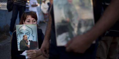 En esta foto del 28 de noviembre de 2016, una mujer sostiene una imagen del fallecido líder cubano Fidel Castro, mientras espera en una fila para rendirle el último homenaje en La Habana, Cuba. Foto:Rodrigo Abd / AP Foto