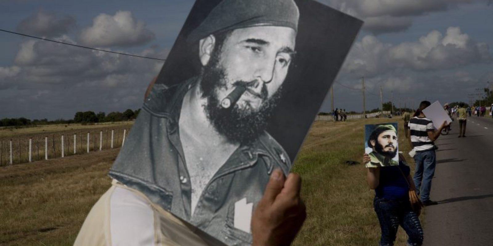 n esta foto del 2 de diciembre de 2016, un hombre usa una fotografía de Fidel Castro para hacerse sombra del intenso sol, mientras espera la caravana que trasladaba las cenizas del líder de la revolución cubana en un camino cerca de Yarigua, Las Tunas. Sus restos fueron llevados a la ciudad oriental de Santiago de Cuba. Foto:Rodrigo Abd /AP Foto