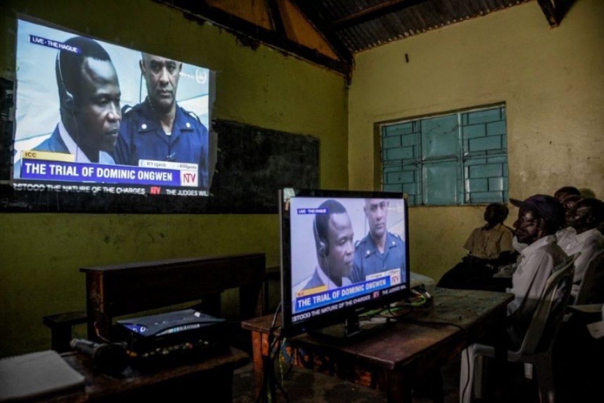 Varias personas miran en la pantalla de televisión el inicio del juicio contra Dominic Ongwen en la Corte Penal Internacional el 6 de diciembre de 206 en Lukodi Foto:Isaac Kasamani/afp.com