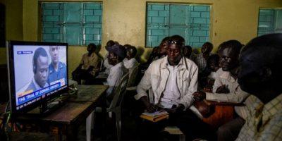 Varias personas siguen por televisión el juicio contra el exniño soldado y jefe de guerra ugandés Dominic Ongwen ante la CPi el 6 de diciembre de 2016 en Lukodi Foto:Isaac Kasamani/afp.com