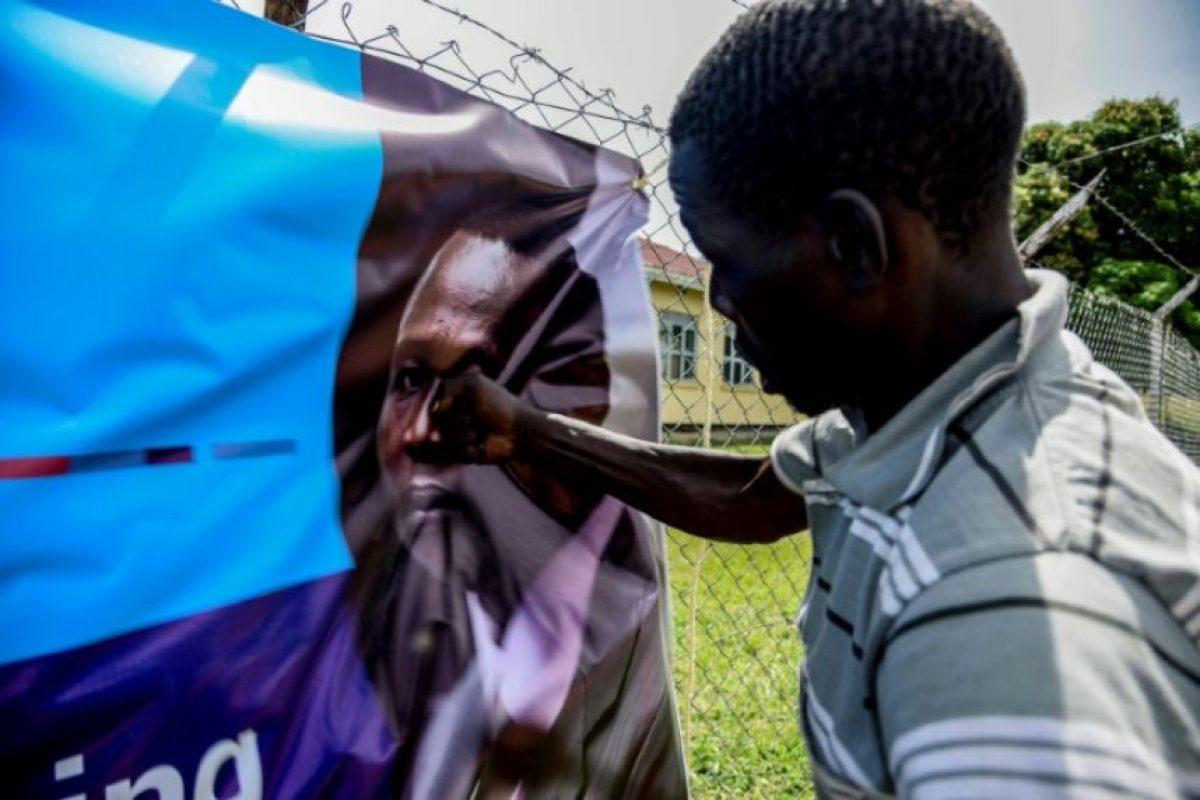 Un hombre golpea un cartel con la imagen del líder del Ejército de Resistencia del Señor el 6 de diciembre de 2016 en Lukodi Foto:Isaac Kasamani/afp.com