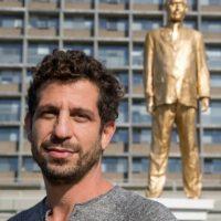 El artista Itai Zalait posa con el fondo de su estatua dorada del primer ministro israelí Benjamin Netanyahu, hecha como forma de protesta contra el dirigente y colocada sin permiso oficial fuera de la alcaldía de Tel Aviv, el 6 de diciembre de 2016. Foto:JACK GUEZ/afp.com
