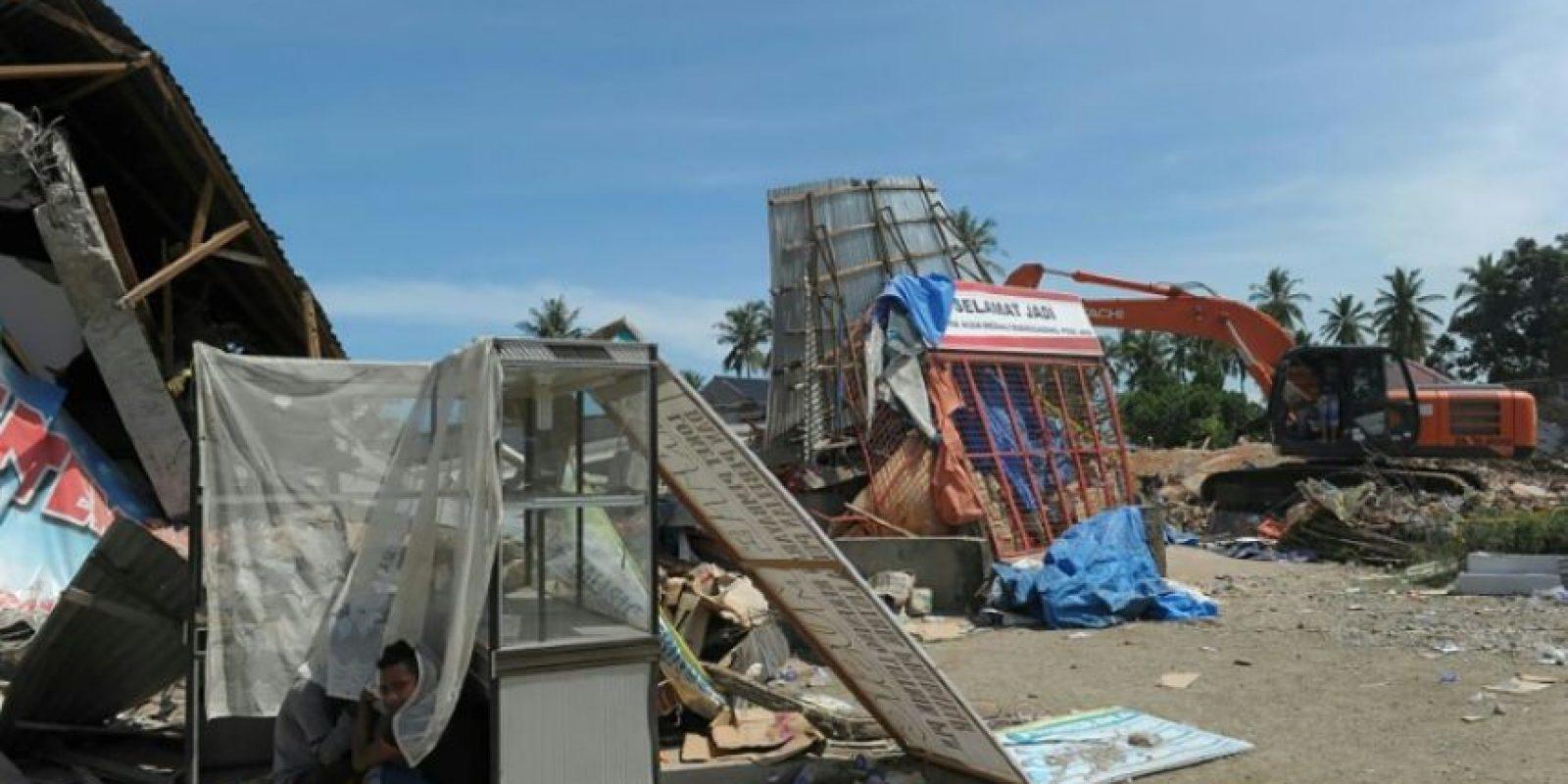 Unos jóvenes damnificados por el terremoto se ponen a cubierto por el calor entre los restos de dos tiendas en Pidie Jaya, en la provincia indonesia de Aceh, el 7 de diciembre de 2016 Foto:Chaideer Mahyuddin/afp.com