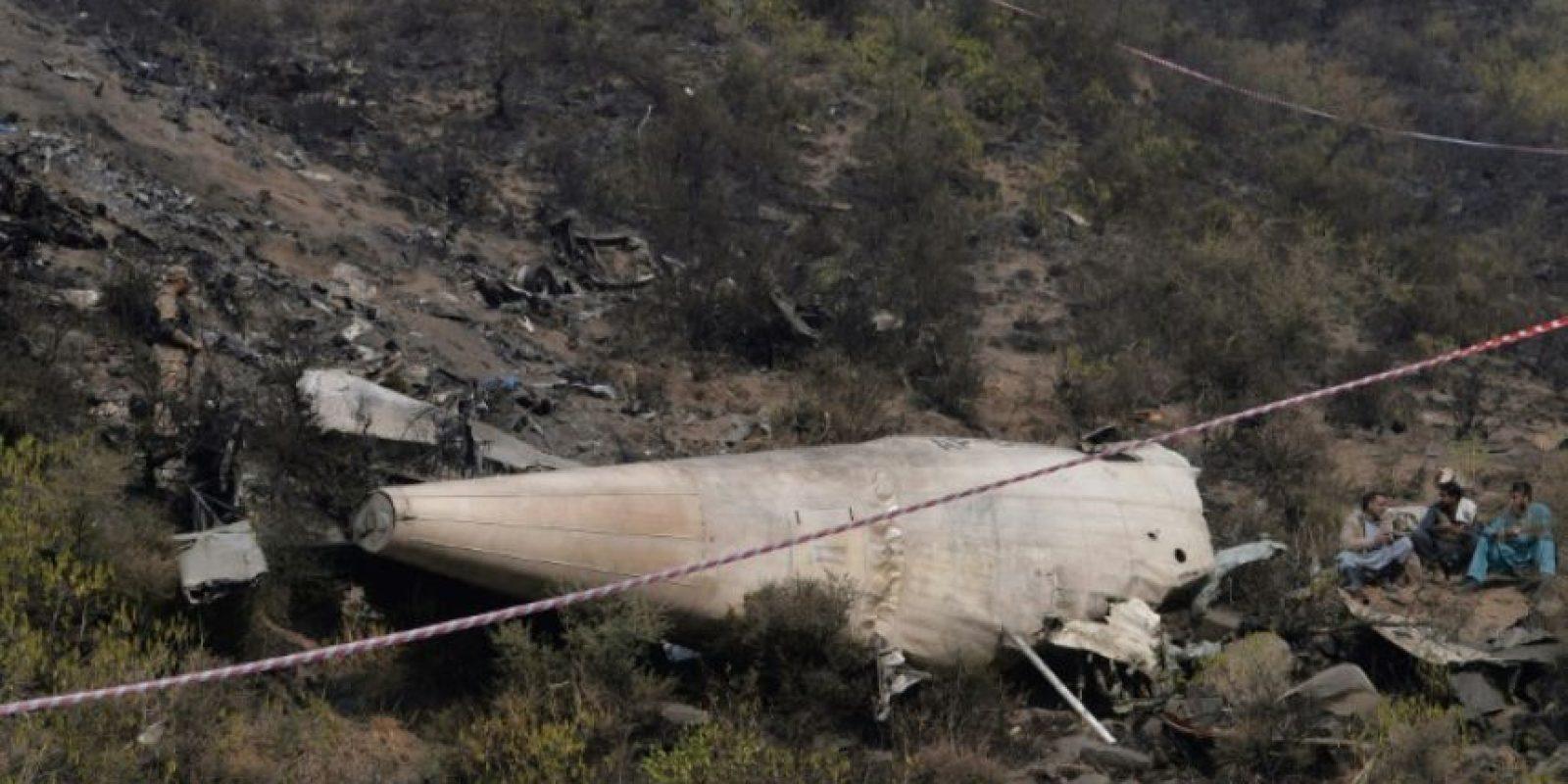 Unos hombres permanecen junto a los restos del avión siniestrado, este jueves 8 de diciembre cerca del pueblo de Saddha Batolni, al norte de Pakistán Foto:Aamir Qureshi/afp.com