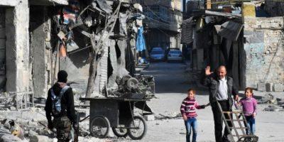 Un hombre saluda a integrantes del Ejército sirio que patrullan las calles de barrios retomados de Alepo en Siria el 8 de diciembre de 2016 Foto:George Ourfalian/afp.com