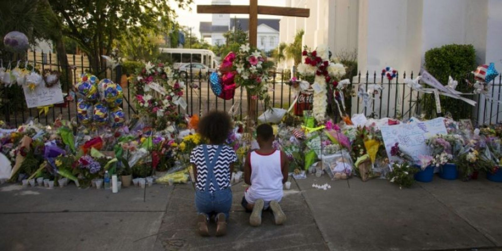 Dos niños rezan delante miles de flores y cartas de condolencias, afuera de la iglesia metodista episcopal africana Madre Emanuel, en Charleston, Estados Unidos, el 23 de junio del 2015 Foto:Jim Watson/afp.com