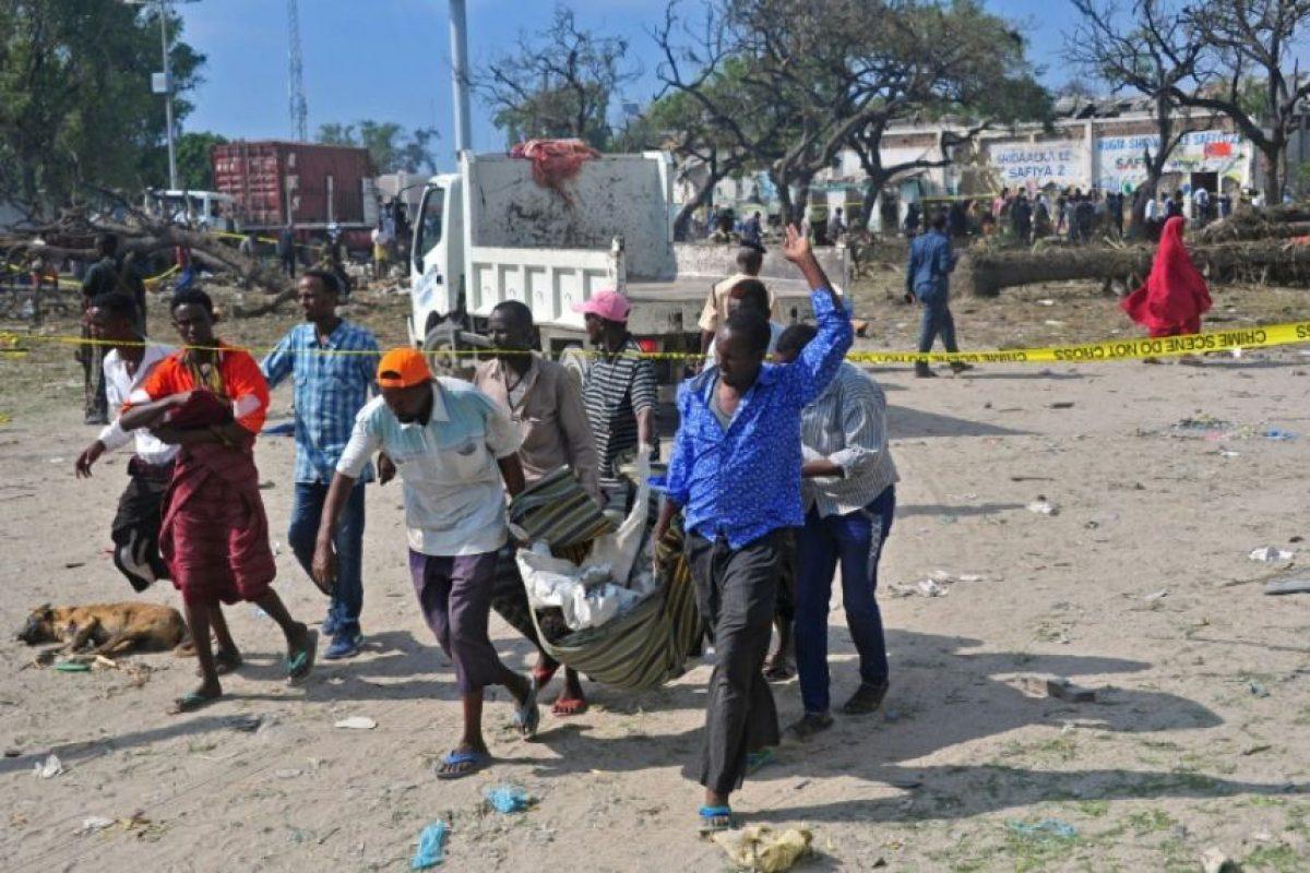 Varias personas evacúan el cuerpo de uno de los 16 fallecidos en un atentado suicida en el puerto de Mogadiscio, el 11 dse diciembre de 2016 Foto:Mohamed Abdiwahab/afp.com