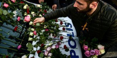 Un hombre deja flores sobre un vehículo de la policía en un homenaje a los agentes muertos en el atentado de Estambul el fin de semana, ante el estadio Vodafone Arena, del Besiktas, el 11 de diciembre de 2016 Foto:Yasin Akgul/afp.com