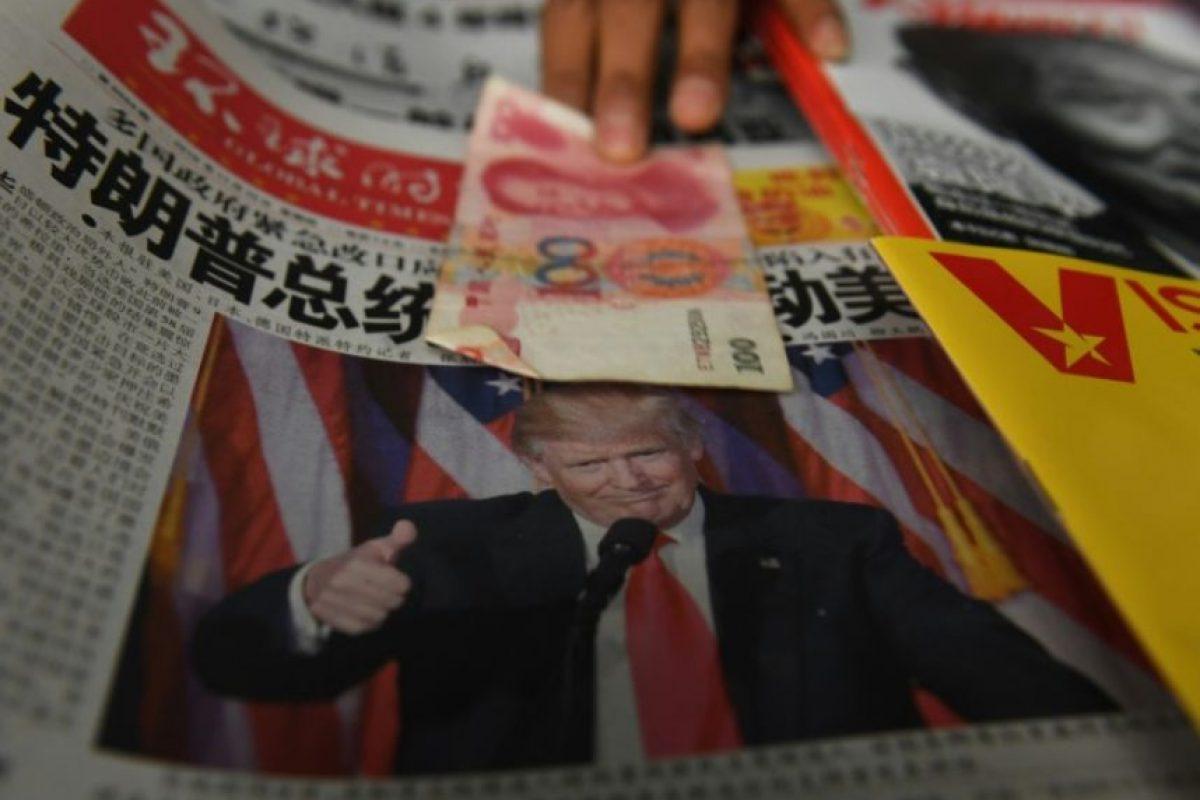Un vendedor extiende un billete de 100 yuanes sobre un periódico con la imagen del presidente electo estadounidense, Donald Trump, en un kiosco en Pekín el 10 de noviembre de 2016 Foto:Greg Baker/afp.com