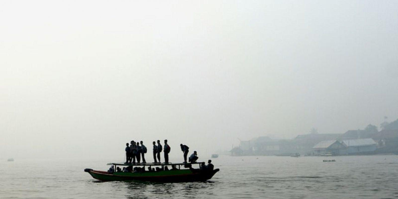 Estudiantes indonesios verifican fuego forestal desde un barco. Foto:AFP