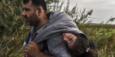 Refugiado carga a una niña en la frontera de Serbia y Macedonia. Foto:AFP