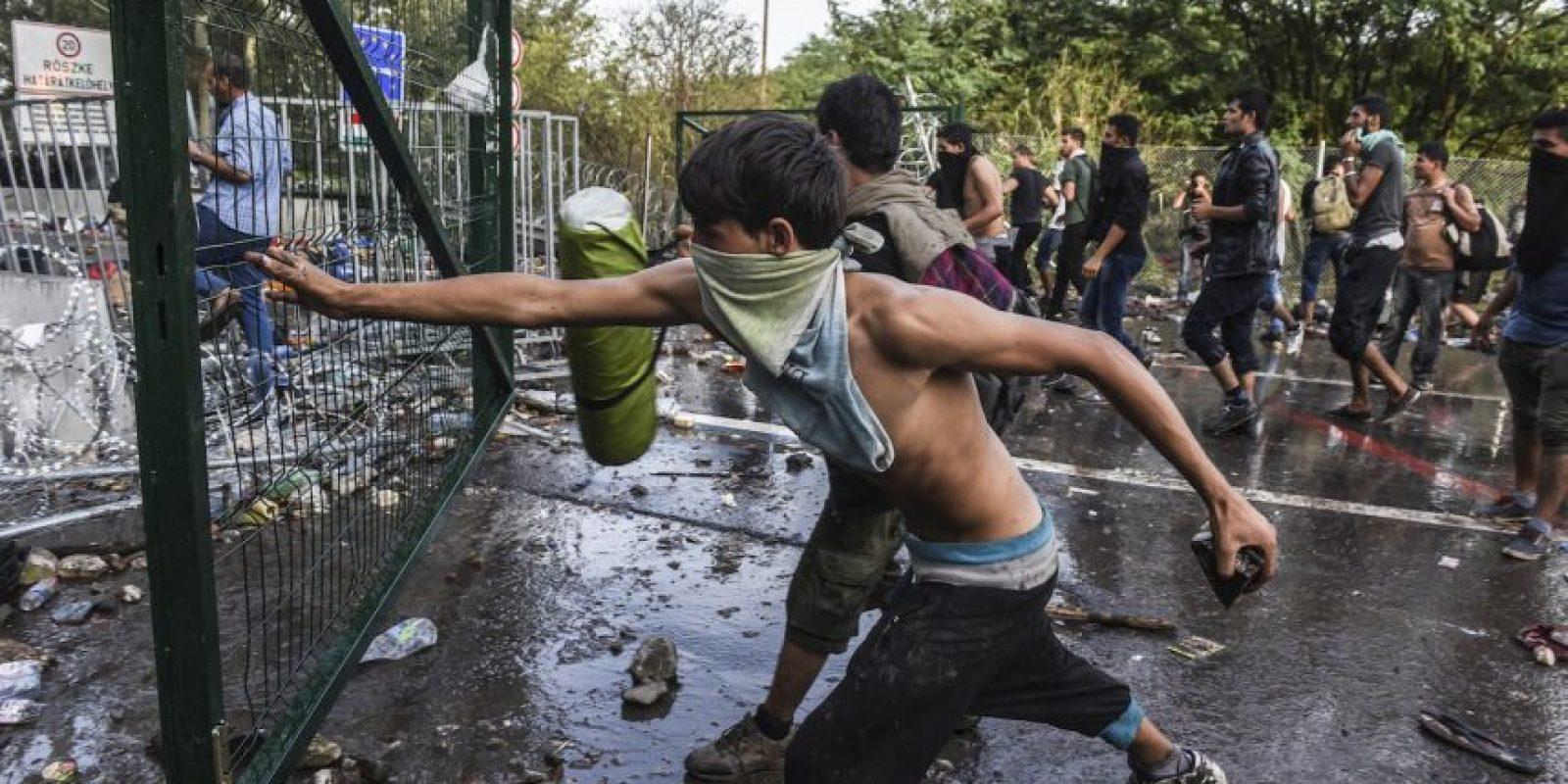 Migrantes lanzan rocas a la policía antidisturbios en Hungría. Foto:AFP