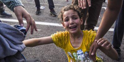 Niña llora al haber sido rociada con gas pimienta en Hungría. Foto:AFP