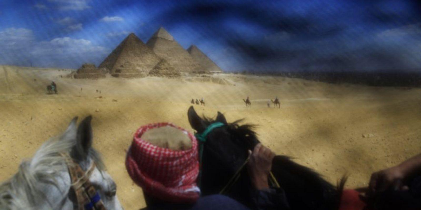 Un guía cerca de El Cairo (Egipto), en las pirámides de Giza. Una típica imagen vista de una manera diferente a la habitual, a través de un 'niqab'. Una trama que separa los ojos de estas mujeres del mundo que las rodea. Foto:AP Photo/Hassan Ammar