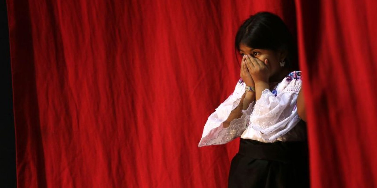 En esta imagen del sábado 23 de mayo de 2015, una niña otavalo tras oír el nombre de su hermana, mientras contempla el desfile final del concurso de belleza Reina Indígena en el teatro Casa de la Cultura en Quito, Ecuador. Las jóvenes ecuatorianas competían ataviadas con vestidos y tocados nativos. Foto:AP Foto/Dolores Ochoa