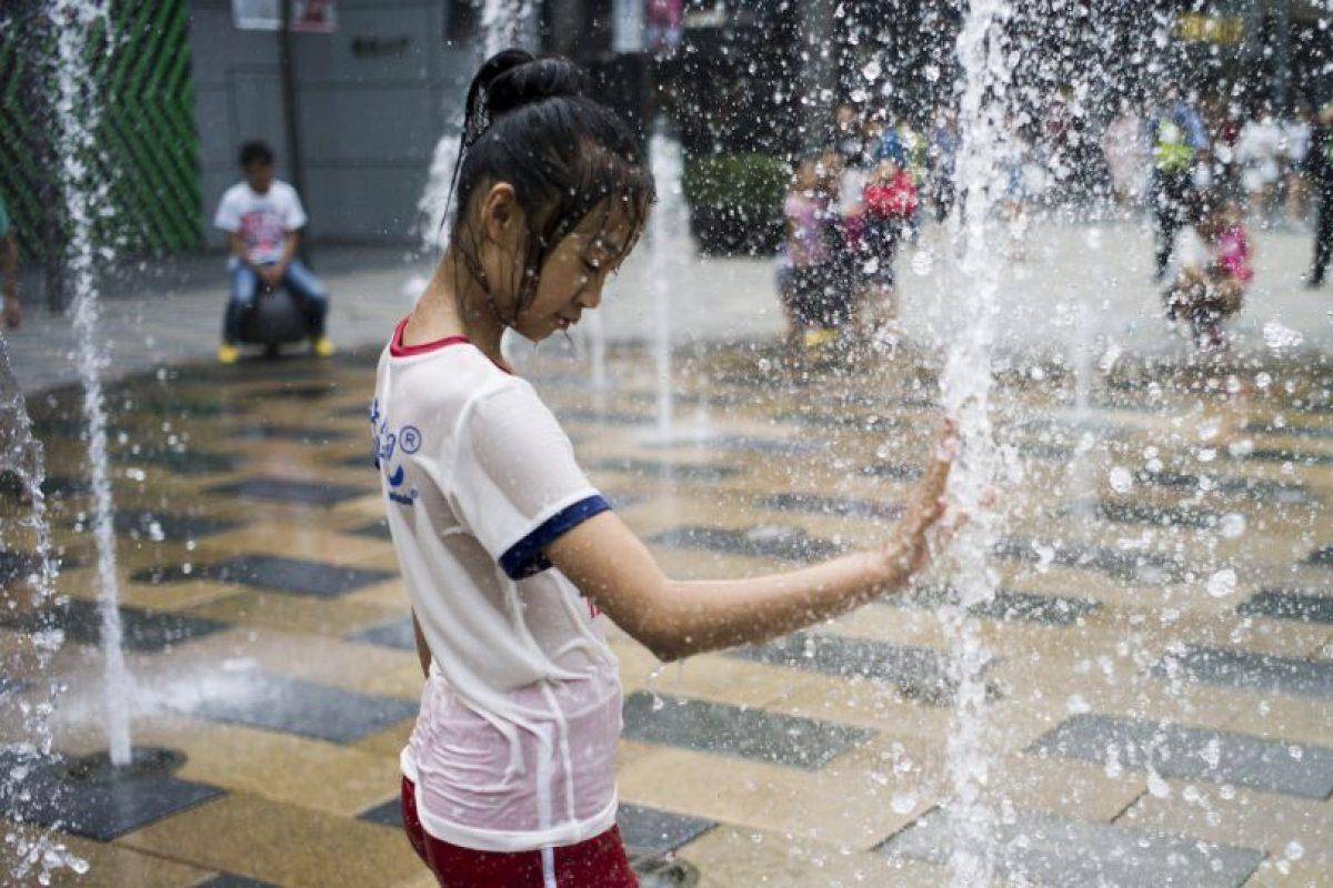 Niña se refersca del calor del verano en China. Foto:AFP