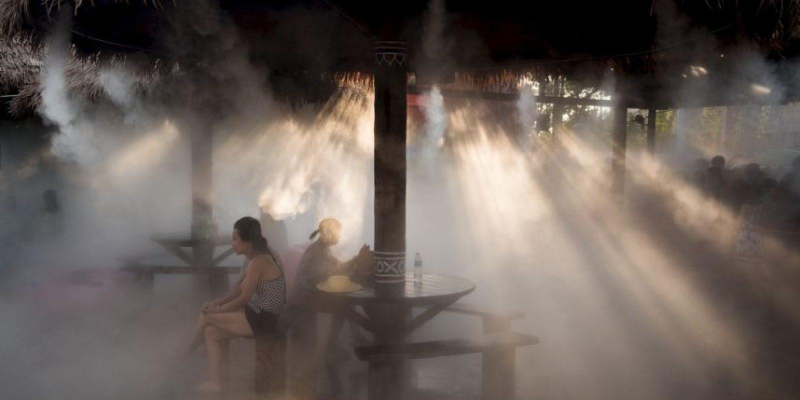 Personas bajo un rociador de agua, esto para refrescarse del calor del verano. Foto:AFP