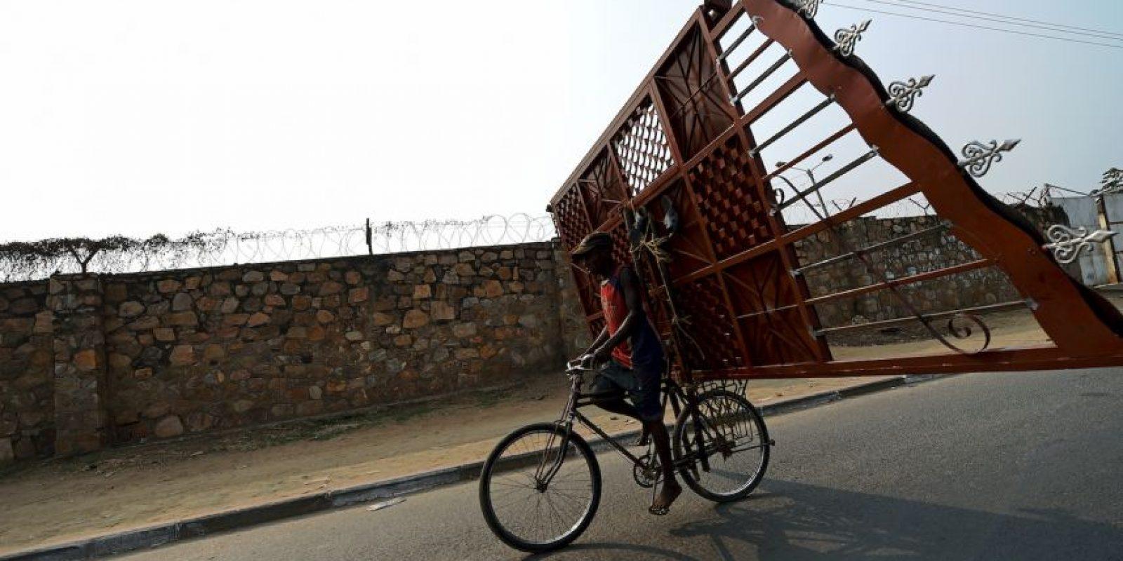 Hombre carga una puerta de metal en su bicicleta en Burundi. Foto:AFP