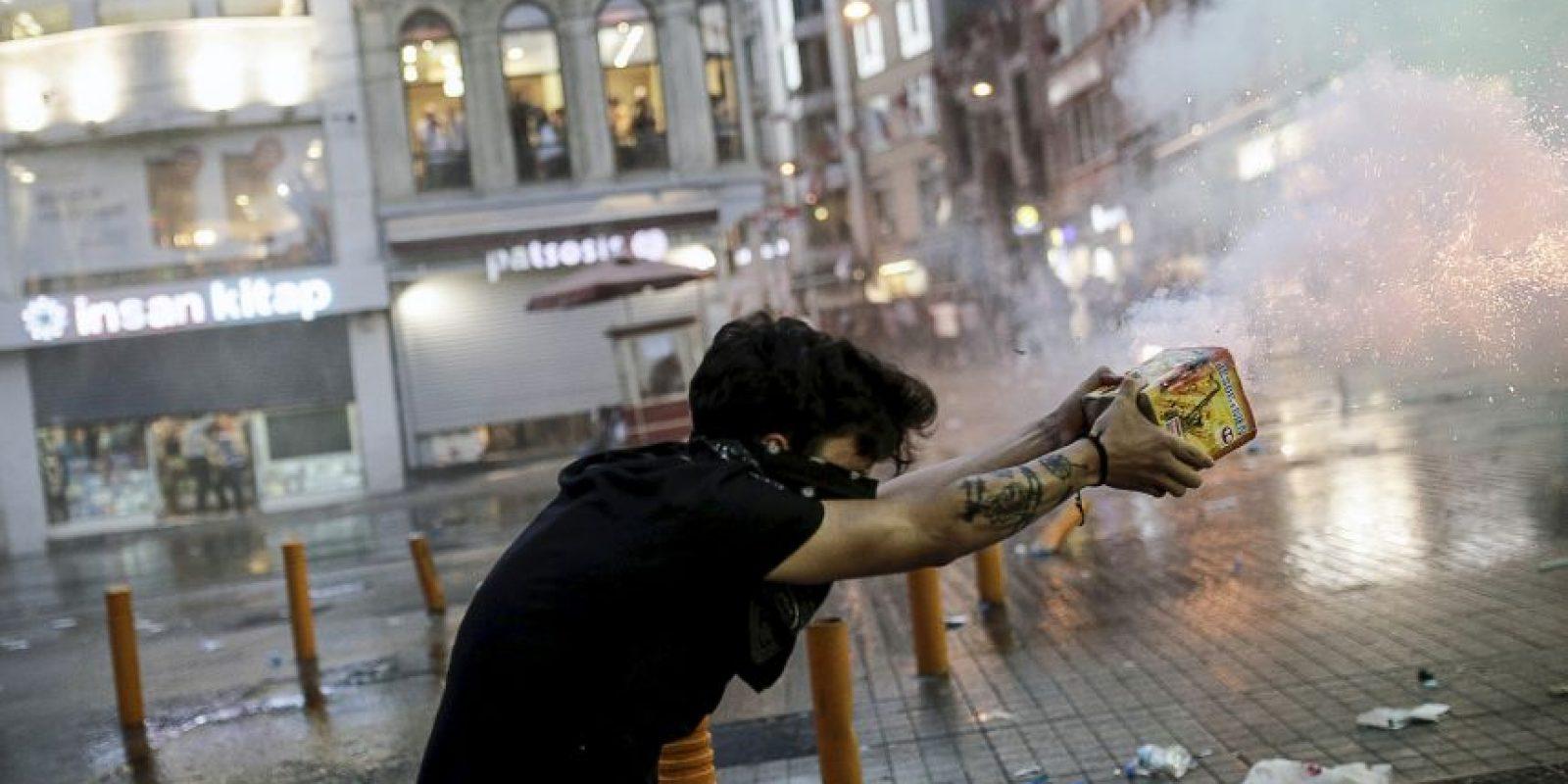 Un manifestante dispara fuegos artificiales a la policía antidisturbios en Estambul. Foto:AFP