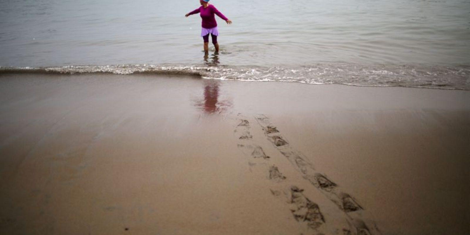 """En esta imagen, tomada el 9 de abril de 2015, Rosa Esquibel, de 50 años, entra al océano Pacífico en la playa Pescadores en Lima, Perú. Bajo el cielo nublado, los bañostas practican talasoterapia, que deriva del griego """"thalasso""""(""""mar"""") y se sumergen en las aguas del océano, con propiedades curativas. Foto:AP/ Rodrigo Abd"""