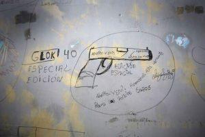 """Esta imagen del 7 de abril de 2015 muestra la pared de una celda cubierta con dibujos y mensajes al interior de la ahora abandonada Prisión García Moreno, durante una visita guiada al público en Quito, Ecuador. Los mensajes alrededor del dibujo alientan a las personas a matar a los policías abusivos con una pistola Glock Edición Especial 50. Una parte del mensaje dice: """"Hermanos. Hasta la muerte. Para la policía abusiva"""". Foto:AP/ Dolores Ochoa"""