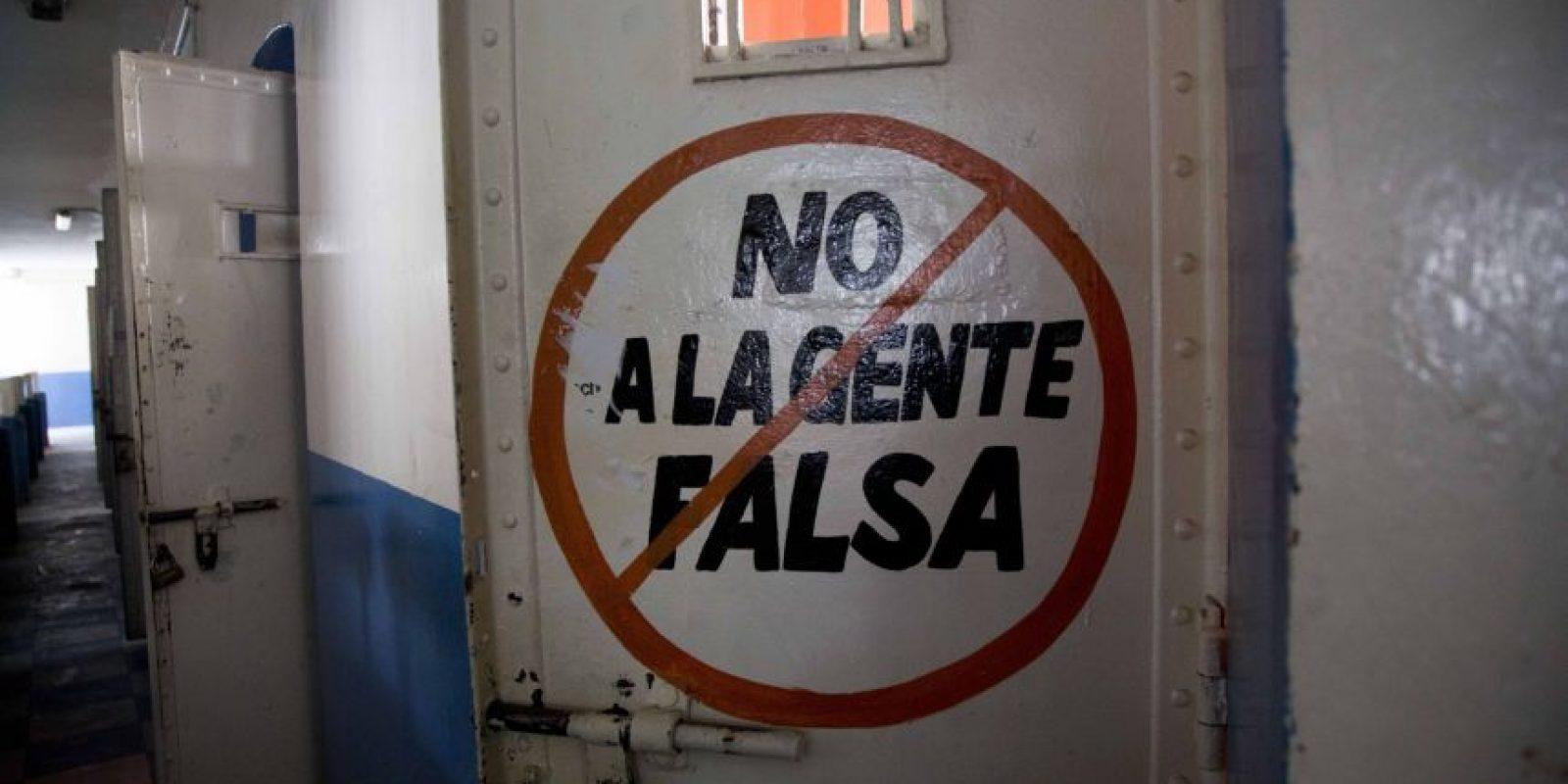 """En esta imagen del 16 de abril de 2015, el exterior de una puerta de celda con las palabras """"No a la gente falsa"""" en la ahora vacía cárcel García Moreno, durante una visita guiada al público en Quito, Ecuador. Presos ricos y pobres, buenos y malos, culpables e inocentes emplearon las paredes del penal para registrar sus días. Foto:AP/ Dolores Ochoa"""