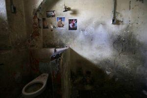 """En esta imagen del 9 de abril de 2015, el baño de una zona de la prisión adornado con fotos de chicas y un auto en la ahora vacía prisión García Moreno, en Quito, Ecuador. El psicólogo Óscar Ortiz, que trabajó con los internos entre estas paredes, dijo que la mayoría de la gente cree que la cárcel es el peor lugar con la peor gente, """"pero yo que he vivido muchos años, concluyo que la cárcel es una muestra de lo que es nuestra sociedad"""", afirmó. Foto:AP/ Dolores Ochoa"""