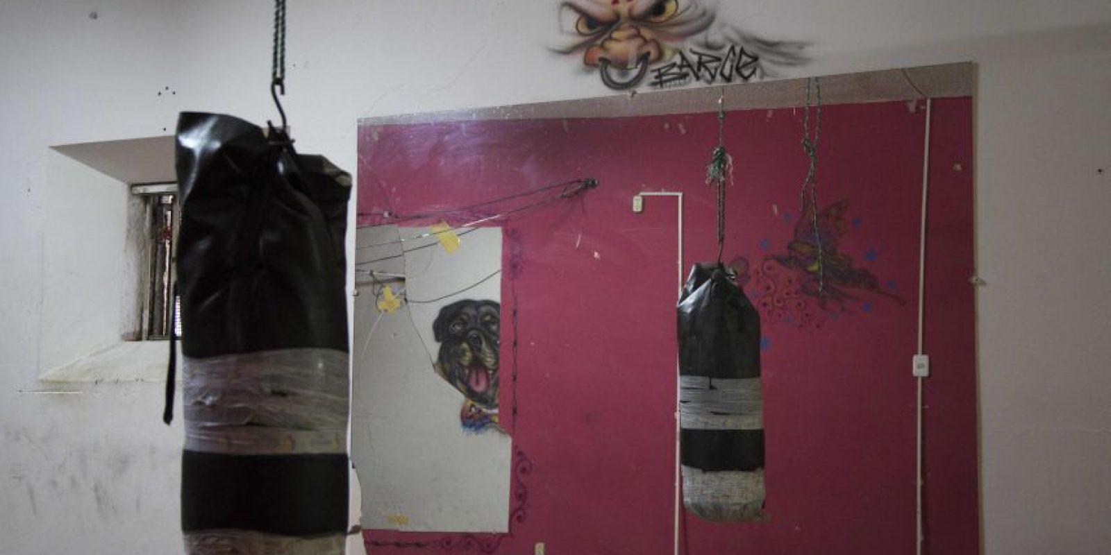 En esta imagen del 14 de abril de 2015, un saco de boxeo cuelga en el gimnasio, reflejado en un espejo, en el ahora vacío penal García Moreno, durante una visita guiada al público en Quito, Ecuador. El acceso al gimnasio estaba considerado como un privilegio para los prisioneros. Foto:AP/ Dolores Ochoa