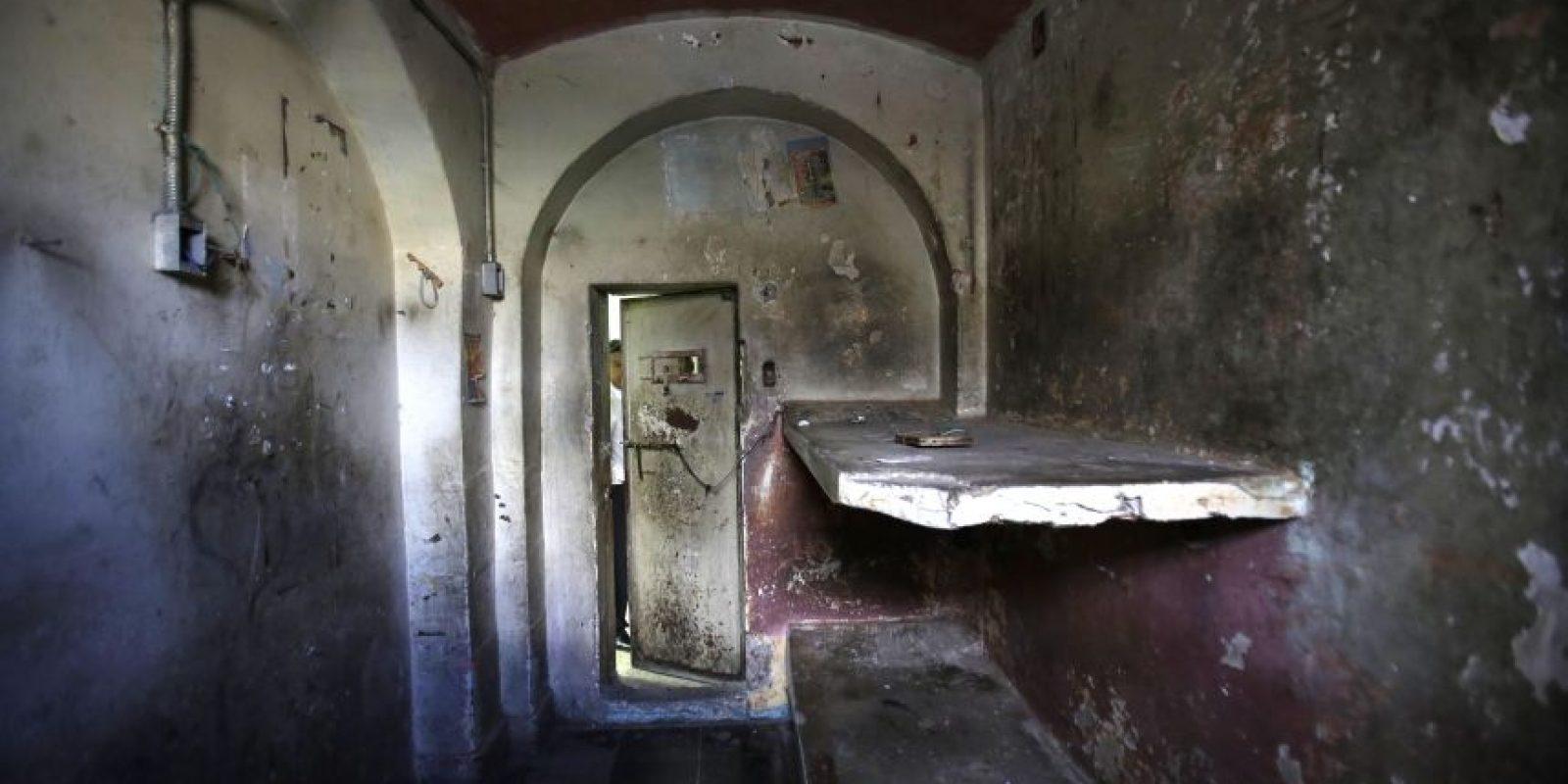 """En esta imagen del 7 de abril, un turista asoma a través de la puerta de una celda en la ahora vacía prisión García Moreno durante una visita guiada al público en Quito, Ecuador. Según los guías, esta celda tenía el apodo de """"Los polillas"""". Aquí, en una celda diseñada para dos reos, la pandilla que controlaba la vida del penal encerraba por la noche a unos 15 internos adictos a las drogas. Los presos también se prostituían para conseguir acceso a drogas. Foto:AP/ Dolores Ochoa"""