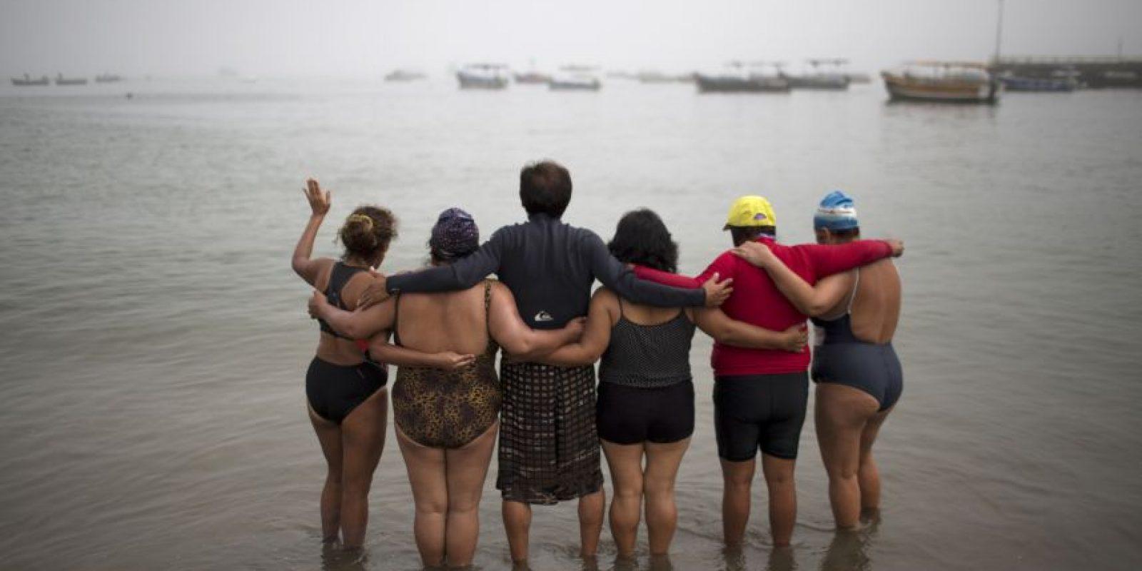 """En esta imagen, tomada el 9 de abril de 2015, un grupo de terapia, ahora convertidos en amigos, rezan en la playa Pescadores antes de tomar un baño terapéutico en aguas del océano Pacífico en Lima, Perú. """"El mar es la farmacia de la humanidad"""", dijo el el promotor de terapias naturales José Cusquisiban, que organiza grupos de terapia. """"Tiene muchos minerales, vitaminas"""". Foto:AP/ Rodrigo Abd"""