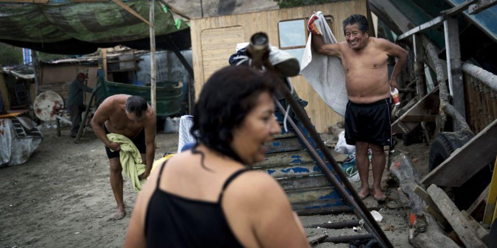 """En esta imagen, tomada el 13 de mayo de 2015, un grupo de personas se viste en la playa Pescadores tras bañarse en aguas del océano Pacífico en Lima, Perú. Bajo el cielo nublado de la capital, los bañistas practican talasoterapia, que deriva del griego """"thalasso"""" (""""mar"""") y se sumergen en las aguas oceánicas con propiedades curativas. Foto:AP/ Rodrigo Abd"""
