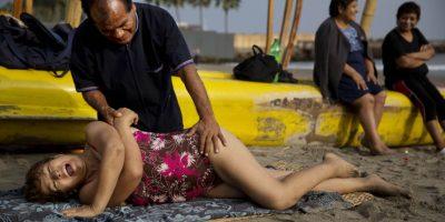 """n esta imagen, tomada el 15 de mayo de 2015, el quiropráctico Félix Retamoso trata a Virginia Espinoza de un dolor en la parte baja de la espalda en la playa Pescadores, donde toma baños terapéuticos en el océano Pacífico, en Lima, Perú. """"No solo es barato, si no que estamos al aire libre en contacto directo con la naturaleza"""", dijo la mujer de 67 años. Foto:AP/ Rodrigo Abd"""