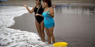 """En esta imagen, tomada el 8 de mayo de 2015, las hermanas Zoraida Infante (izquierda) y Graciela Trujillo rezan en la playa Pescadores antes de un baño terapéutico en el océano Pacífico en Lima, Perú. Bajo un cielo nublado, los bañistas practican talasoterapia, que procede del griego """"thalasso"""" (""""mar""""), y se sumergen en las aguas con propiedades curativas del océano. Foto:AP/ Rodrigo Abd"""
